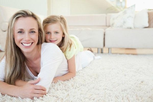 девочка с мамой лежат на чистом ковре