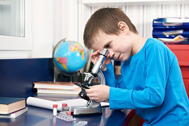 мальчик смотрит в микроскоп