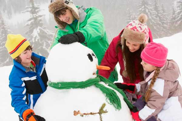 дети лепят снеговика зимой